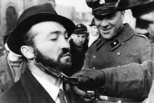 Een Duitse soldaat kijkt lachend toe hoe een collega de baard van een Pools-Joodse man afknipt. Foto genomen in Polen, oktober 1939 Collectie NIOD, Amsterdam