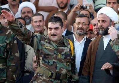 Freed Lebanese prisoner Samir Kantar (L), wearing Hezbollah military fatigues, waves as he stands next to Hezbollah's military chief in south Lebanon Sheikh Nabil Qawuq (C) and freed Lebanese prisoner Hussein Suleiman (R) upon their arrival in Naqura in southern Lebanon on July 16, 2008. Five Lebanese prisoners freed by the Israeli authorities arrived in Lebanon today, hours after Hezbollah handed over the bodies of two Israeli soldiers seized by its guerrillas two years ago. Among those freed in a prisoner swap greeted with triumph in Lebanon but anguish in Israel was Samir Kantar, who was sentenced to five life terms for a 1979 triple murder, including of a child. AFP PHOTO/RAMZI HAIDAR